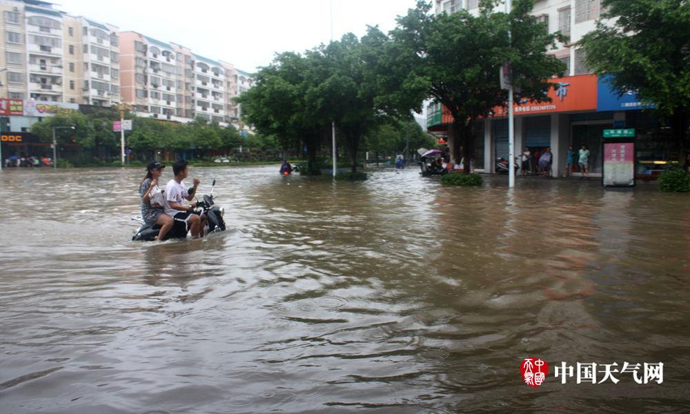 """14日,广西桂林临桂区一对情侣骑着小电驴过""""河"""".(摄影:屈红梅"""